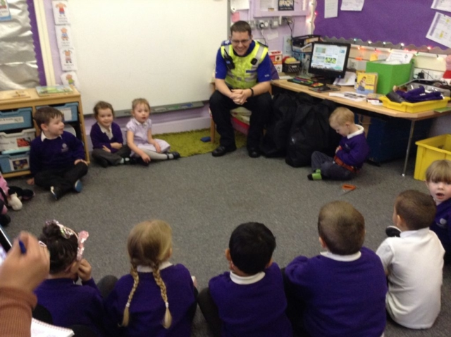 group of children listening to a police officer