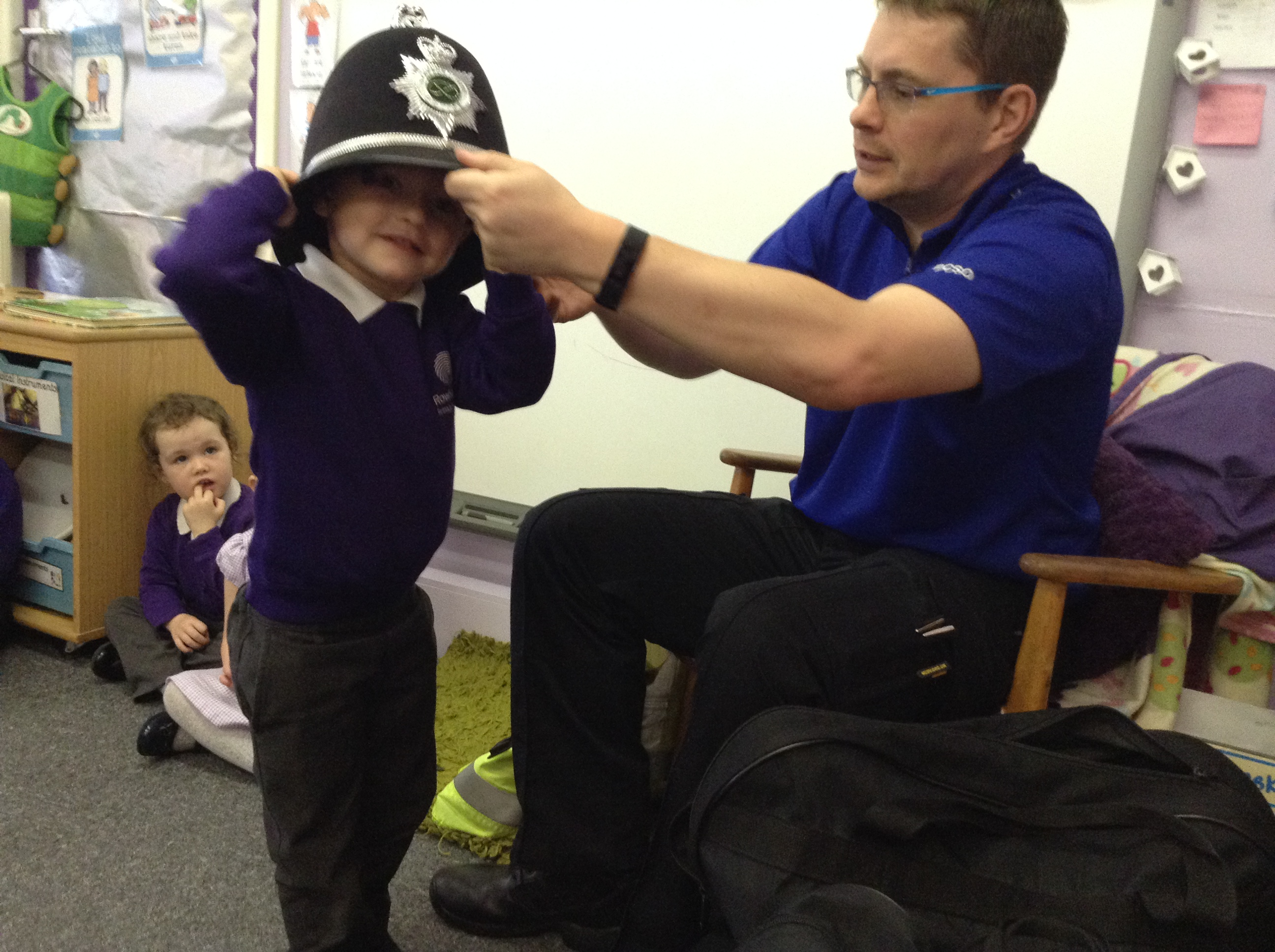 child trying on a police helmet